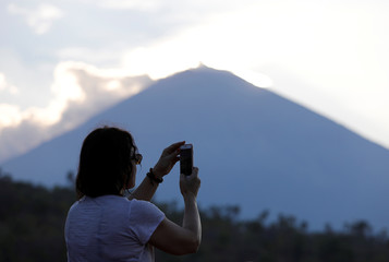 A tourist takes a picture of the sun set near Mount Agung, a volcano on the highest alert level, from Amed on the resort island of Bali