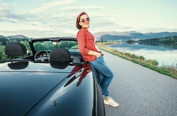 Young woman stand near cabriolet car on the  road with beautiful mountain lake view