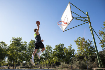 Anonymous man jumping high above ground throwing ball in hoop while playing basketball.