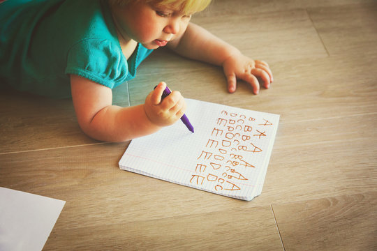 little girl learning to write letters