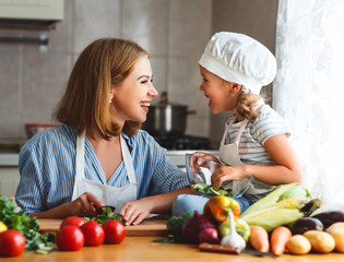 Healthy eating. family mother and child girl preparing vegetarian vegetable salad at home in kitchen