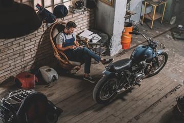 mechanic in repair shop with motorbike