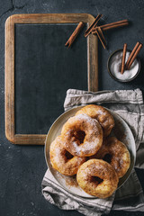 Plate of homemade donuts with sugar and cinnamon powder on vintage chalkboard served with spices and textile napkin over dark texture background. Top view with space for text