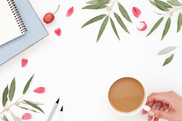 Woman's hand with a cup of coffee. Workplace, note, book, pencil, foliage, white creative background.