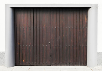 Brown wooden gate in white concrete wall