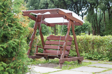 Beautiful wooden swing, surrounded by green trees and shrubs of the garden.