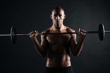 Portrait of a safro american sports man doing exercises with barbell