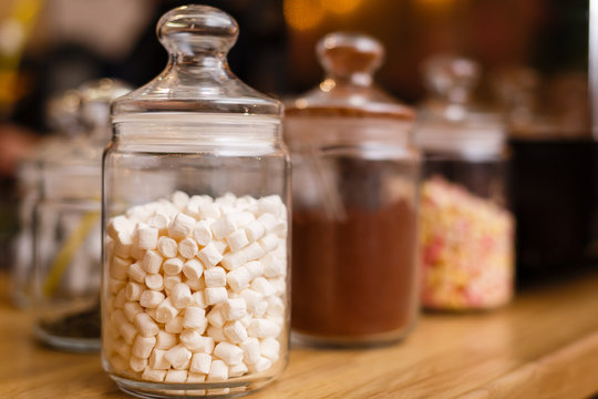 Heap of marshmallows in transparent glass jar on light pink cloth background