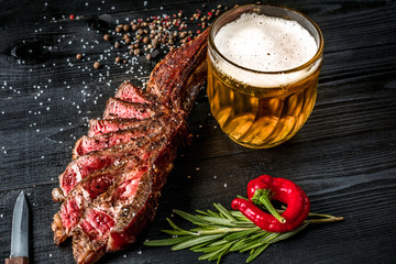 Grilled steak seasoned with spices and fresh herbs served with mug of beer, fresh red pepper