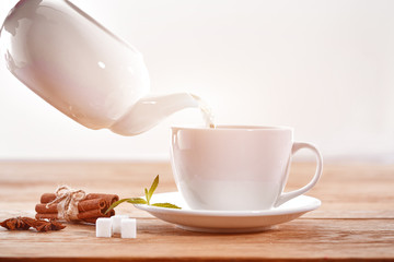 cup with green tea, sugar and teapot on light wooden table background