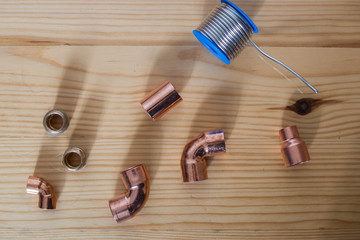Tools on a wooden background for the installation of heating pipes, copper pipe parts and tile