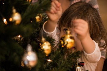 Cute little girl decorating christmas tree