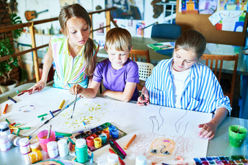 High angle  portrait of three little kids painting pictures in art class sitting at tables with art supplies, pencils and paints