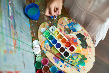 Above view image of watercolor paints tray on top of messy palette with color blots used by unrecognizable child painting on easel during art class