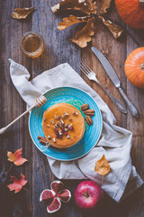 Pumkin pancakes on a blue plate on wooden background served with pecan nuts and honey. Autumn food still life