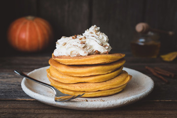 Pumpkin pancakes stack served with whipped cream, pecan nuts and cinnamon. Closeup view, horizontal, toned image