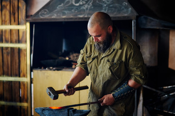Blacksmith working in the forge. Manufacture of parts and weapons from molten metal, using the hammer and anvil.