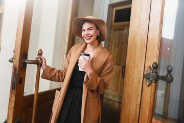 Girl in a brown coat a brown hat is walking and posing in the city interiors. The girl is smiling, checking her smartphone and drinking coffee from take away cafe. The photo looks very positive cause
