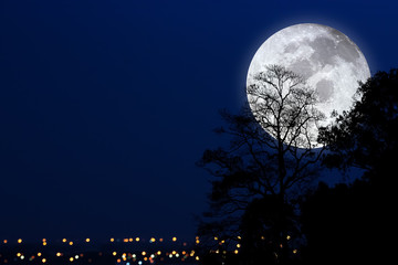 Dramatic atmosphere and beautiful big moon on night sky over big city.Image of full moon furnished by NASA.