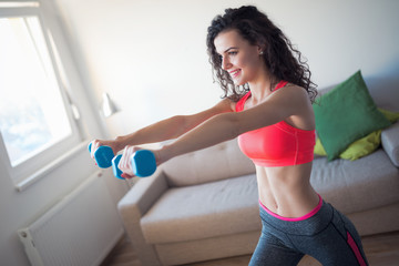 Beautiful smiling woman practicing with dumbbells