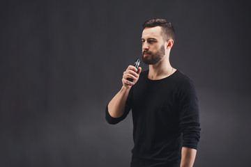 Young man vaping e-cigarette on black