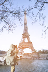 Asian male photographer in coat shooting photos while standing near Eiffel tower, Paris. France with copy space area for your text.