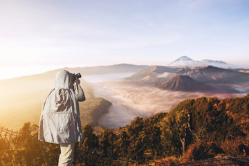 Asian male photographer in coat shooting photos while standing near Mount Bromo, is an active volcano and part of the Tengger massif, in East Java, Indonesia. And with copy space area for your text.