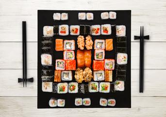 Set of sushi, maki and rolls on white wood background