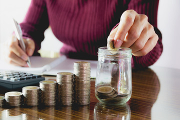 Woman process and drop coin into the glass with stack coins and calculator. Woman working on table.
