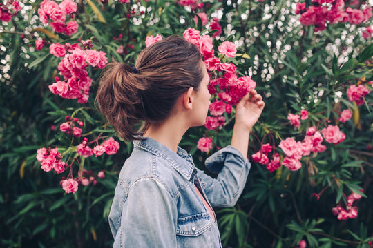 Woman touching pink flowers
