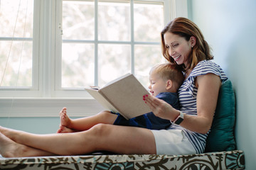 Mother sitting on a window sill reading a book to her son