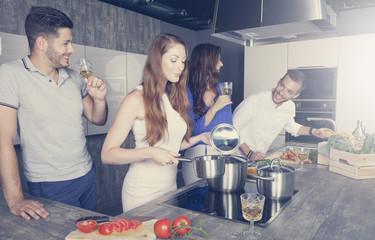 two couples have fun in the kitchen while cooking and drinking white wine