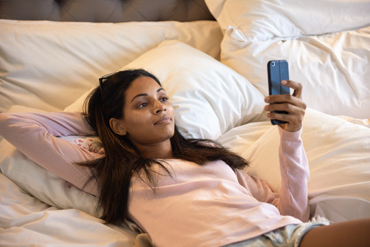 Young woman lying in bed using her mobile cell phone