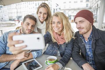group of friends taking selfie in coffee shop