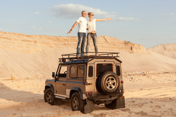 Man and a woman in the desert on a car enjoy life.