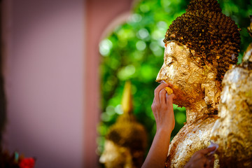 Thai people make merit, Buddhists gilding gold leaf on the face of Buddha statue to worship Buddha in Buddhist temple , people hand Gilding hand buddha selective focus Religious ceremony of Thailand.