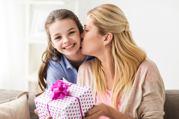 girl giving birthday present to mother at home