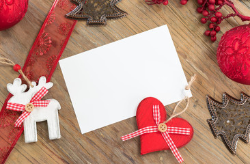 Christmas background with objects for decoration in Christmas tree, white sheet of blank paper and red festive ribbon on wooden table top. Space for text.