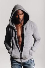 Muscular young man wearing hooded shirt looking down