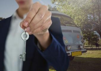 Businesswoman Hand  Holding key in front of camper van