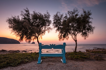 A Bench Overlooks the Sunset next to the Sea