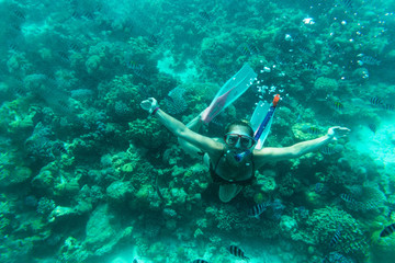 The girl floats under water on coral reefs