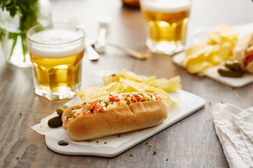 Lobster roll on plastic board with pickles