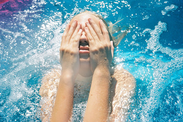 girl with hands on face in blue water with sparkles