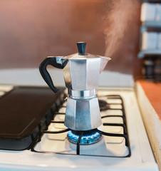 Steaming Italian coffee percolator on gas stove