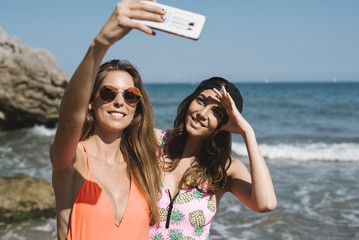 Two girls taking a self portrait at the beach