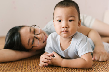 Toddler boy and his mother playing on bed