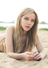 beautiful young blond woman lying on the beach