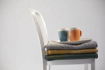 Two ceramic mugs and a plate on a stack of cotton blanquets