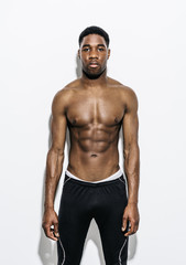 Handsome young Afro-American sportsman posing topless on white background